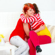 Two cute girlfriends sitting on sofa and happily embracing — Stock Photo #8651340