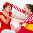 Two happy girlfriends sitting on sofa and cheerfully embracing — Stock Photo #8651345
