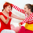 Two happy girlfriends sitting on sofa and cheerfully embracing - Stock Photo