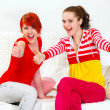 Two smiling girlfriends sitting on sofa and showing thumbs up gesture - Stock Photo