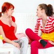 Funny girl sitting on sofa and showing  tongue her amazed girlfriend - Stock Photo
