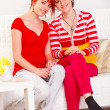 Two happy girlfriends sitting on sofa at living room - Stock Photo
