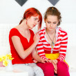 Attentive girl sitting on sofa and soothing her sad girlfriend - Stock Photo