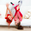 Funny girlfriends in playful mood lying on sofa with legs raised up — Stock Photo