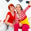 Stock Photo: Funny girlfriends showing tongues while photographing themselves