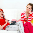 Stockfoto: Bored girl sitting on sofa while her girlfriend phone talking