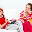 Stock Photo: Bored girl sitting on sofa while her girlfriend phone talking