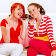 Sitting on sofa two girlfriends holding headphones and listening music — Stock Photo