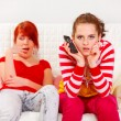 Bored girl yawning while her girlfriend attentively watching TV — Stock Photo #8651537