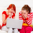 Laughing girlfriends looking on laptop — Stock Photo