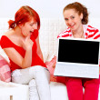 Two cheerful girlfriends showing laptops blank screen — Stok fotoğraf