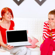 Two smiling girlfriends showing laptops blank screen — Stock Photo