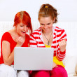 Two happy girlfriends using laptops and showing yes gesture - Stock Photo