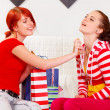 Cheerful girl applying new perfume on her girlfriend - Stock Photo