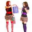 Pretty young girl with shopping bags presenting one to her girlfriend — Stock Photo