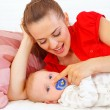 Young mother laying on couch and playing with baby — Stock Photo