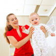 Smiling mother helping baby learn to walk — Stock Photo