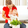 Smiling mommy showing plant to her baby — Stock Photo
