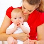 赤ちゃんの口の中で母のラップの上に座っている間彼の手を入れて — ストック写真