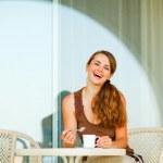 テラスの上に座って、お茶のカップを持つ美しい女性の笑みを浮かべてください。 — ストック写真