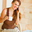 Smiling woman sitting on terrace with laptop and cup of tea and — Stock Photo