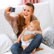 Beautiful young mom making photos with her lovely baby - Zdjęcie stockowe