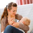 Young mother sitting on sofa and feeding her baby — Stock Photo #8653004