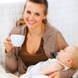 Happy mother resting while baby sleep by having tea and reading - Zdjęcie stockowe