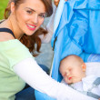 Smiling mother sitting near stroller and taking care about her baby - Stock Photo
