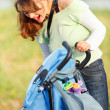 Laughing mother looking in stroller while walking in park — Stock Photo