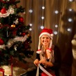 Pretty woman near Christmas tree making gift - Photo