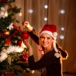 Beautiful woman hanging Christmas ball on Christmas tree — Stock Photo
