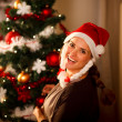 Smiling young woman decorating Christmas tree — Stock Photo #8653150