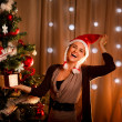 Happy girl in Santa hat near Christmas tree with present box — Stock Photo #8653163