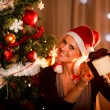 Interested woman near Christmas tree shaking present box trying — Stock Photo