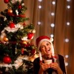 Portrait of happy girl near Christmas tree with present box — Stock Photo