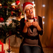 Happy young woman near Christmas tree hugging present box - Photo