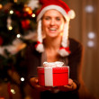 Hand presenting gift box and smiling woman and Christmas tree in — Stock Photo #8653228