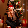 Beautiful female in Santa Hat near Christmas tree and present bo - Zdjęcie stockowe