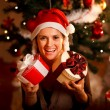 Portrait of pretty girl near Christmas tree holding present boxe — Stock Photo #8653275