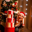 Pretty woman near Christmas tree looking out from pile of presen — Stock Photo #8653285