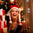 Portrait of laughing woman near Christmas tree looking out from — Stock Photo #8653292