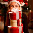Woman near Christmas tree hiding behind pile of present boxes — Stock Photo #8653306