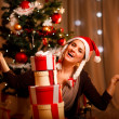 Happy female near Christmas tree with tower of present boxes — Stock Photo #8653311