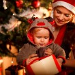 Young mother helping interested baby open present box at Christm — Stock Photo