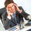 Businessman with headache sitting at office desk and holding hands at head — Stock Photo #8653814