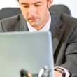 Portrait of modern businessman sitting at office desk and workin — Stock Photo #8653839