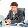 Modern businessman sitting at office desk and pointing finger on laptop — Stock Photo #8653848