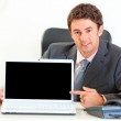 Smiling businessman sitting at office desk and pointing finger on laptop wi — Stock Photo #8653864