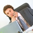 Thoughtful modern businessman with headset working on laptop — Stock Photo #8653876